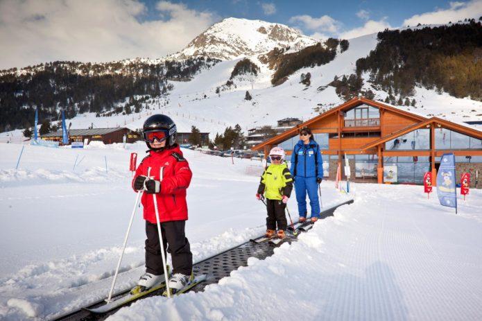 Двое детей и женщина на эскалаторе горнолыжного курорта Андорры