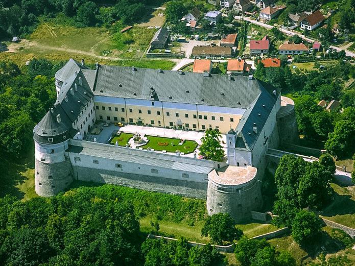 Здание замка «Червеный камень» с мощными башнями, окруженное парком и домами