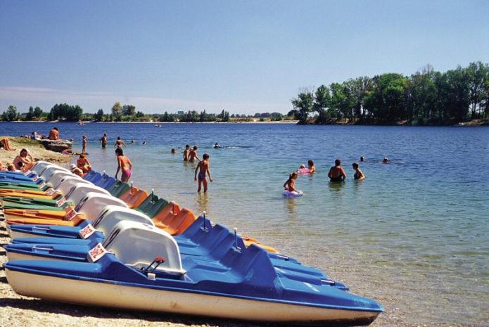 Катамараны на берегу озера и люди в воде