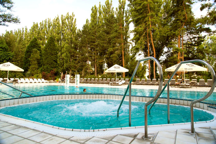 Девушка плавает в бассейне с термальной водой