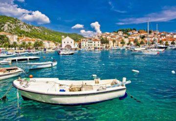 Лодка, море и город Хорватии на заднем фоне