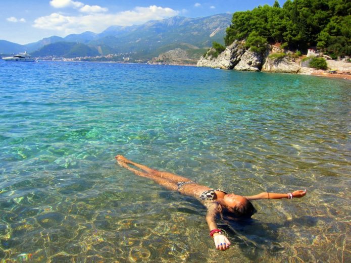 Девушка лежит на воде в прозрачном море